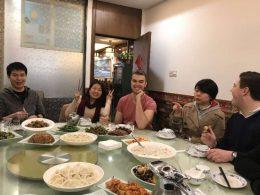 Professores e alunos desfrutando do jantar juntos